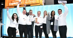 Men and women wearing white shirts and dark pant, arms in the air, smiling faces
