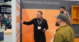 One man pointing at an expo sales booth wall, two other men look at what he's pointing at