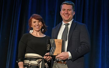 Woman on left, man on right holding an award plaque