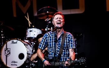 Man wearing a blue plaid shirt plays guitar and sings