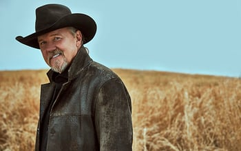 Man wearing a cowboy hat and dark leather jacket
