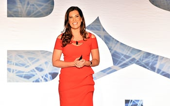 Woman with brown hair wearing a red dress faces audience