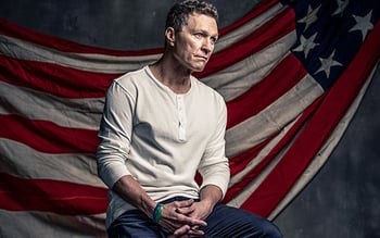 Man wearing a white shirt sitting down with American flag behind him