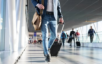 Man dragging a suitcase walking through airport