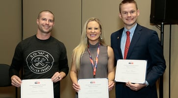 Two men and a woman holding certificate awards.