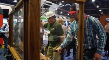 Two men wearing hats and goggles hammer nails into a piece of wood