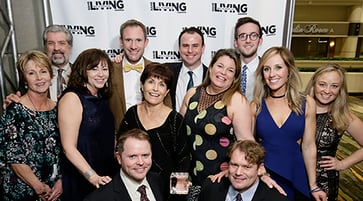 Men and women standing in a group in front of a Best in American Living Awards backdrop.