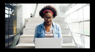 Woman sitting on stairs, typing on laptop