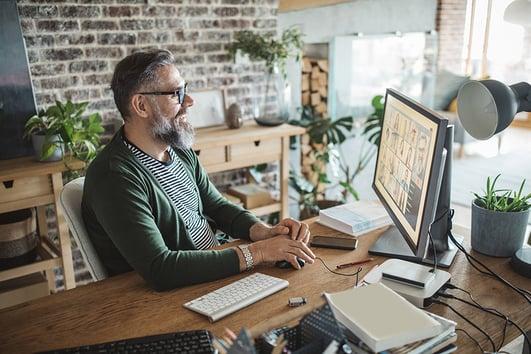 Man wearing glasses sits at a desk looking at his computer