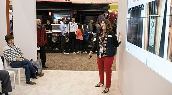 Woman with red pants and flowered shirt stands next to screen facing audience