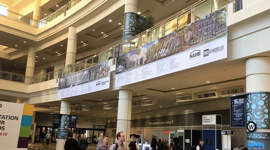 Banners displayed above people walking around exhibit hall
