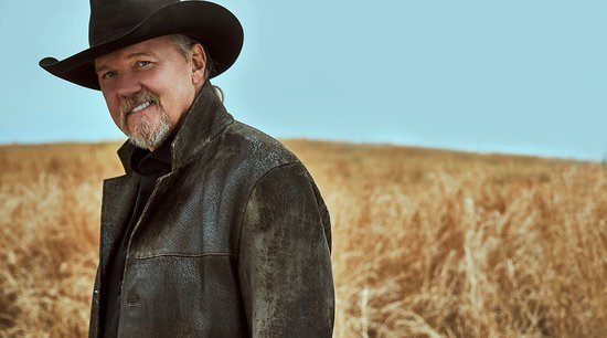 Man standing in a wheat field wearing a black hat and brown jacket smiling