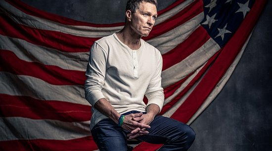 Man wearing a white shirt and jeans sits on stool with an American flag behind him